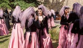 Women in beautiful Georgian dresses talking in crowd of people during popular wine festival stock image