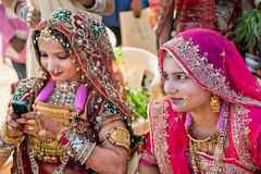 Women in beautiful indian dresses and gold jewelry. JAISALMER, INDIA - MAR 1: Women in beautiful indian dresses and gold jewelry sitting in shadow on the Desert Royalty Free Stock Photography