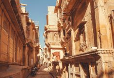Women on beautiful narrow street with old haveli houses, historical indian homes royalty free stock image
