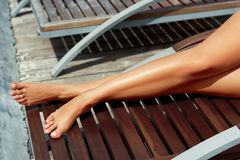 Women Beautiful Sexy Legs on the Pool. Skin care and Protection Sun. Spa Concept. Epilation Laser or Shaving ConceptSunscreen on Feet royalty free stock images