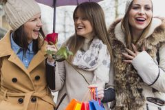 Bad weather will not stop us from shopping. Women, beautiful women, group of people, beauty; warmly dressed; coats; jacket; caps; windy weather; view shop royalty free stock photo