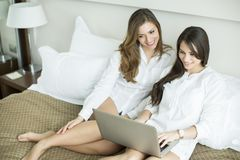 Women in the bed with laptop Royalty Free Stock Photos