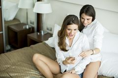 Women in the bed with mobile phone Royalty Free Stock Images
