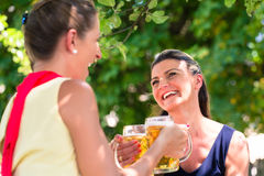 Women in beergarden having refreshment. Sitting under tree in the shade as it is hot Royalty Free Stock Photos