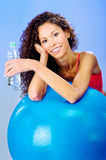 Women behind blue pilates ball holding bottle of water Royalty Free Stock Photo