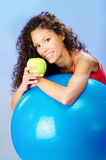 Women behind blue pilates ball holding green apple. Smiled pretty curls hair woman behind blue pilates ball holding green apple Royalty Free Stock Photography