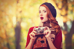 Women in beret with camera. Redhead woman in beret with camera in the park Stock Images
