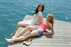 Women on the berth at sunny vacation day Stock Images