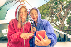 Women best friends enjoying with smartphone with sun coming out Royalty Free Stock Photos