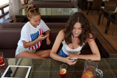 Women best friends using cell telephones while sitting in coffee shop, digital tablet with copy space screen Stock Images