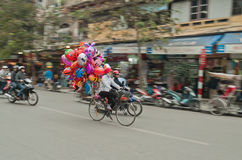 Women on a bicycle with colorful balloons on the street. Hanoi. Vietnam Stock Photo
