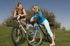 Women With Bicycles Communicating In Park Stock Photo
