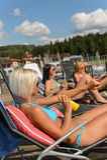 Sunbathing women applying sunscreen bikini Royalty Free Stock Images