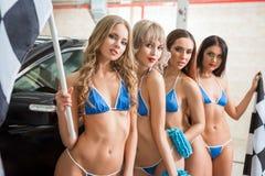 Women in bikini posing with race flags at car wash. Sexy women in bikini posing to camera with race flags at car wash service Royalty Free Stock Image