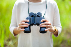 Women and binoculars in hands on green background Stock Photography