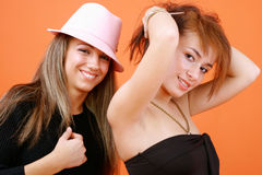 Women In Black. Portrait of two young women in black outfits, smiling with playful expressions.  One woman is wearing a pink hat Stock Image