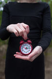 Women in black dress with alarm clock. Women in black dress holding red alarm clock by one hand royalty free stock photo