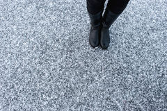 Women black leather boots standing on rough snow background. Gritty  covered asphalt surface. Textplace. Top view. Royalty Free Stock Images