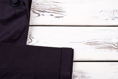 Women black trousers and copy space. Female clothes on white wooden table, space for text royalty free stock photos