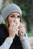 Women blowing into tissue. Sick woman with a cold blowing into tissue Stock Photo