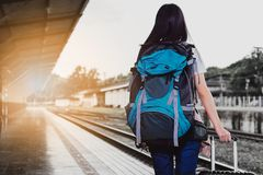 Women, blue backpack and hat at the train station royalty free stock images