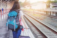 Women, blue backpack and hat at the train station stock photography