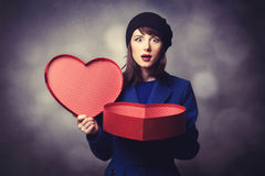 Women in blue dress with heart shape gift Royalty Free Stock Photography