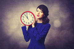 Women in blue dress with huge clock Stock Images