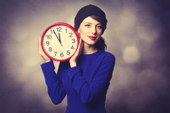 Women in blue dress with huge clock Royalty Free Stock Photos