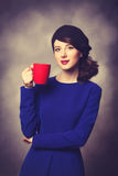 Women in blue dress with red cup Royalty Free Stock Images