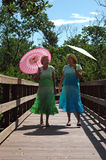 Women on boardwalk. Two mature women talking, smiling and walking along a boardwalk with colorful parasols stock image