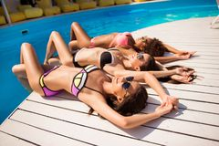 Women body care, beauty, health, skin protection, summer, sun co. Ncept. High angle shot of three girlfriends with perfect smooth soft skin, getting tanned by Royalty Free Stock Image