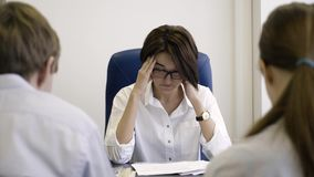 Women boss in stress of job employees. Businesswoman tired of mistakes in work of employees. Attractive boss suffers. From headache and fatigue, removes glasses stock video