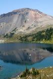 Women on Boulder at Ring Lake. Ring Lake and Ring Mountain. British Columbia Stock Photos
