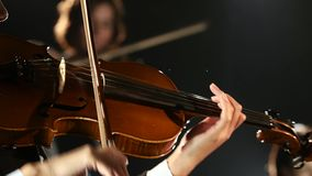 Women bows over the strings of a violin in a room. Black background. Close up stock video footage