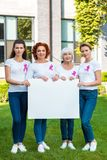 Women with breast cancer awareness ribbons holding blank banner and looking. At camera stock images
