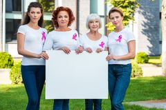 Women with breast cancer awareness ribbons holding blank banner and smiling. At camera royalty free stock images
