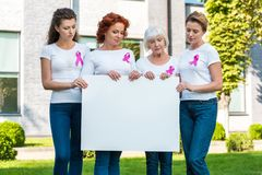 Women with breast cancer awareness ribbons holding blank banner. And looking down royalty free stock photos