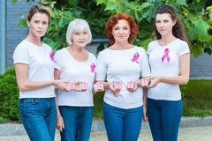 Women with breast cancer awareness ribbons holding cubes with word cancer and looking. At camera stock images