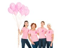 Women with breast cancer awareness ribbons holding pink balloons and smiling at camera. Isolated on white stock photos