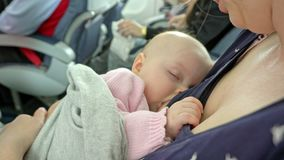 A Woman Breastfeeding her Child on a Plane. A women breastfeeding her child on a plane. Close-up shot royalty free stock photo