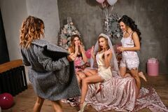 Women and a bride in sexy lingerie looking at their girl friend in coat who showing herself to them. Hen-party