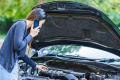 Women and broke down car on the road and she use mobile phone. stock image