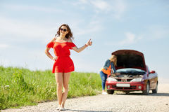 Women with broken car hitchhiking at countryside Royalty Free Stock Image