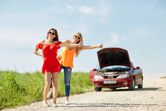 Women with broken car hitchhiking at countryside Royalty Free Stock Images