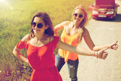 Women with broken car hitchhiking at countryside Stock Images