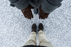 Women brown gloves and men casual  boots standing on asphalt covered gritty snow surface. Cold Winter. Top view. Stock Photos