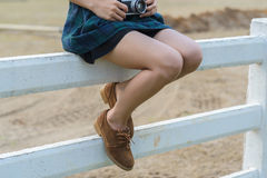 Women with brown shoe on the white fence. Young women with brown shoe on the white fence Stock Photo