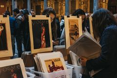 Women browse posters at second hand book market in the courtyard of the Vieille Bourse old stock exchange in Lille, France. The market is hugely popular with Royalty Free Stock Photos