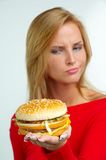 Women and burger. Young woman with burger on hand Royalty Free Stock Image